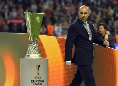 Ajax coach Peter Bosz walks past the trophy at the end of the Europa League final.