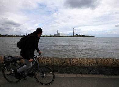 A cyclist glaces at the Poolbeg incinerator plant from the promenade.