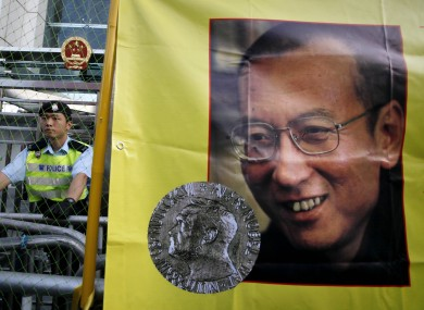 File photo of a police officer standing guard beside a picture of Liu Xiaobo.