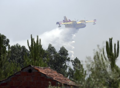 A firefighting airplane drops its load of water trying to prevent a forest fire from reaching a rural Portuguese village earlier today.