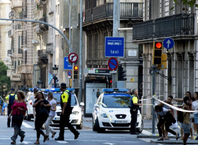 Police officers asking people to leave Plaza Catalonia following the nearby attack