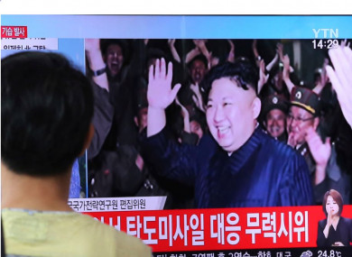 A man in Seoul watches a TV programme showing an image of North Korean leader Kim Jong-un