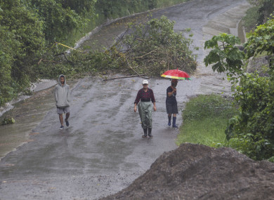 People walk along a washed out road on the outskirts of San Jose, Costa Rica