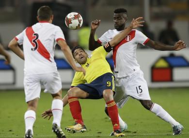 Peru's Aldo Corzo fights for the ball with Colombia's Radamel Falcao as Peru's Pedro Cuba looks on.