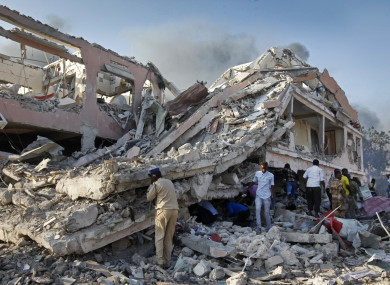 Somalis gather and search for survivors by destroyed buildings at the scene of a blast in the capital Mogadishu, Somalia.