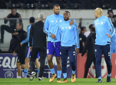 Marseille's Patrice Evra, centre right, is led away by his teammate Rolando after an altercation with Marseille supporters who trespassed into the field.