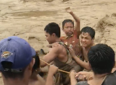 Villagers cross raging flood waters in Lanao del Norte, Zamboanga Peninsula, southern Philippines.