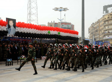 Syrian troops march past a portrait of Bashar al-Assad.