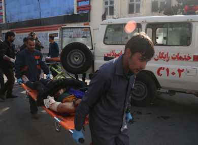 People carry an injured man from the blast site near Sidarat Square in Kabul, Afghanistan.