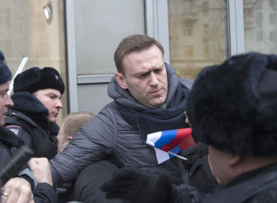 Russian opposition leader Alexei Navalny, centre, is detained by police officers in Moscow, Russia.