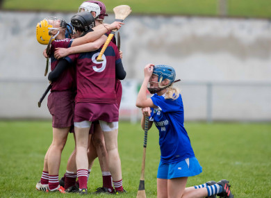 Slaughtneil players celebrate as Niamh Donnelly kneels dejected.