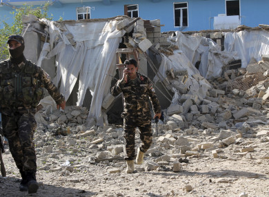 Security forces inspect in an explosion site in Lashkar Gah
