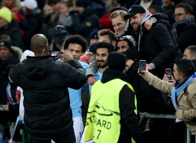 City's Leroy Sane and Ilkay Gundogan pose for a photograph with fans in the stands.