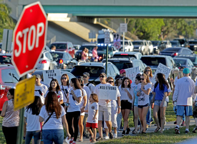 A large group of people demonstrating outside the school at the weekend