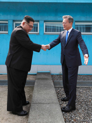 North Korean leader Kim Jong Un, left, shakes hands with South Korean President Moon Jae-in over the military demarcation line at the border village of Panmunjom in Demilitarized Zone.