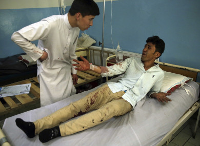 A wounded man, who lost two his daughters, lies on a bed in a hospital after the deadly suicide attack