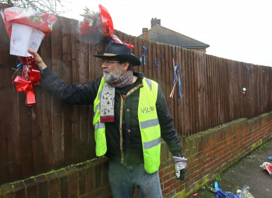 Iain Gordon pulls the flowers down from a fence opposite the house of Richard Osborn-Brooks in South Park Crescent in Hither Green, London.