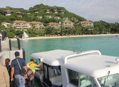 Tourists board a speedboat near a forestland area on Boracay island in Malay town, Aklan province, central Philippines