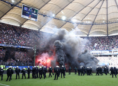 Police intervene as fans throw flares onto the pitch at the Volksparkstadion.