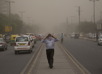 A man wraps a scarf around his nose as a dust storm envelops the city in New Delhi, India.
