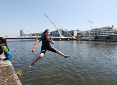 Abbie Butler aged 13 from Dublin jumps into the Liffey at the Convention Centre.