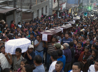 People carry to the cemetery the coffins of seven people who died during the eruption of the Volcan de Fuego on Monday in Guatemala.