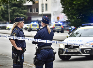 Police stand next to a cordon after five people were shot and injured on an open street in central Malmo.