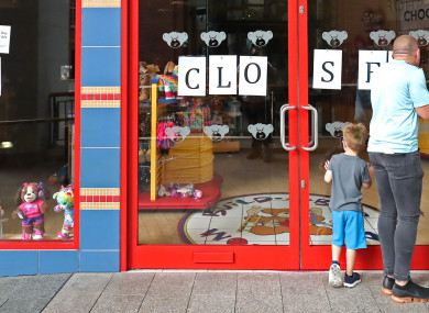 Passersby at the closed shop in Belfast