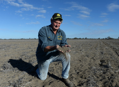 Farmer Rob Turnbull holds dry soil in his hands on what would have been a wheat field.