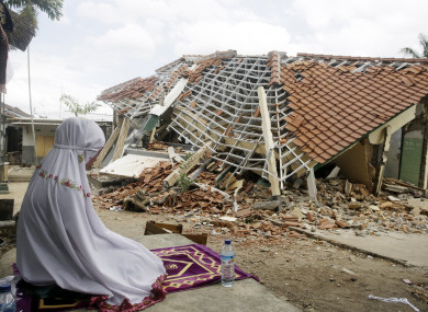 A woman performs a prayer in front of a ruined building following an earthquake in Lombok on 11 August