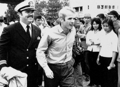 In this 14 March 1973 photo US Navy Lt Cmdr John McCain (centre) is escorted by Lt Cmdr Jay Coupe Jr to Hanoi's Gia Lam Airport after McCain was released from captivity in Vietnam.