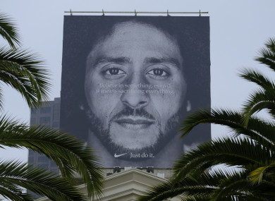 Palm trees frame a large billboard on top of a Nike store that shows former San Francisco 49ers quarterback Colin Kaepernick.