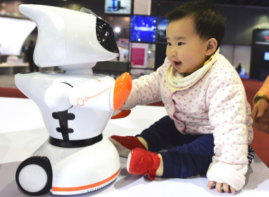 A child interacts with a robot during the China Yiwu International Manufacturing Equipment Expo 2017.