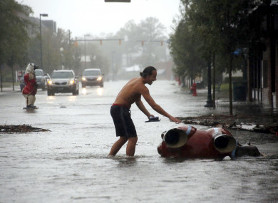A local in New Bern, North Carolina checks a statue that was toppled by Hurricane Florence