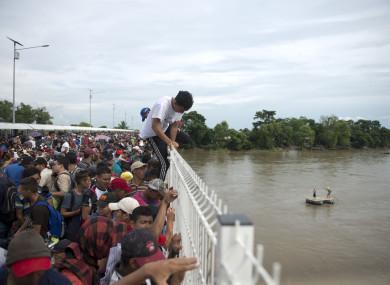 Migrants climbing a border bridge in Guatemala