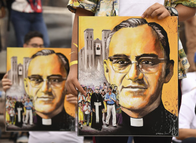 People hold pictures of Archbishop Oscar Romero in San Salvador.
