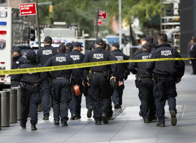 NYPD officers depart after police personnel removed an explosive device from Time Warner Center Friday, Oct. 24, 2018, in New York.