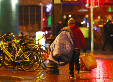 A homeless person walking through the streets of Dublin.