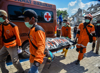Rescue members transfer a body at a collapsed hotel in Palu, Central Sulawesi.