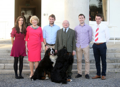 President Michael D Higgins with members of Skibbereen rowing club and his dogs Síoda and Bród.