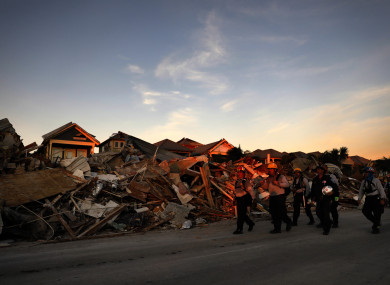 A search and rescue team walks past a debris pile from hurricane Michael