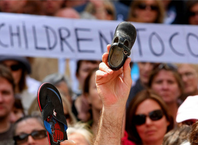 A child's shoe is held up as thousands of victims of institutional abuse survivors during the silent demonstrations in memory of the victims in Dublin city centre to the Dail in 2009.