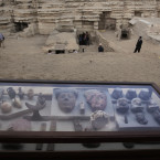 Artifacts on display in their glass case in front of newly discovered tombs.<span class=