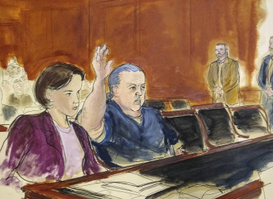 In this courtroom sketch, pipe bombs suspect Cesar Sayoc seated in court, raises his arm to swear to the truth of his statement of need for assigned counsel.