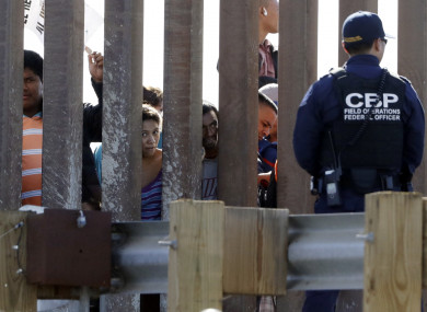 Migrants from Central America look through a border wall into the US