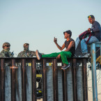 Asylum seekers from Central America speaking with US border patrol at the border fence in Tijuana. <span class=