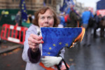 A Leave demonstrator burns an EU flag during the People's Vote protest outside the Houses of Parliament, London, where the debate continues on Theresa May's Brexit deal before the final vote tomorrow.