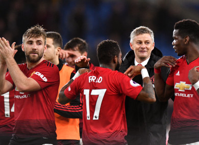 The interim manager celebrates with the United players.