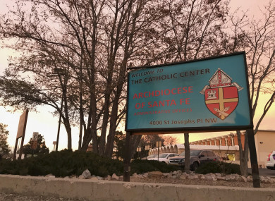 The sun sets on a sign in front of the Archdiocese of Santa Fe offices in Albuquerque, New Mexico