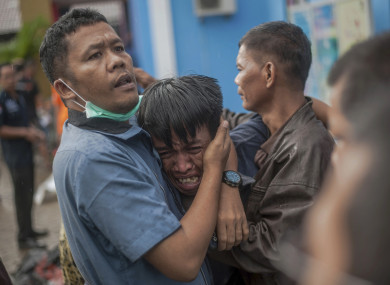 A man reacts are identifying the body of a family member in Carita, Indonesia.